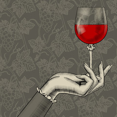 Women's hand with a wine glass on grapes background