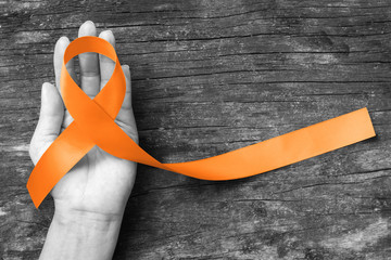 Orange ribbon for Leukemia, Kidney cancer, RDS multiple sclerosis awareness on helping hand symbolic bow color for supporting on patient with disease