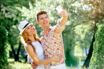 Youth and technology. Young smiling loving couple taking selfie in park