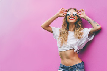 Fun and colorful. Young pretty happy woman in shorts posing agai