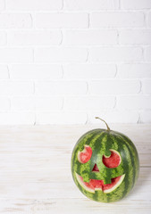 Smiling face of a water-melon on a Halloween like a pumpkin for