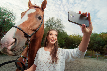 Funny selfie with my friend! Attractive smiling young woman holding smartphone and making selfie with her horse outdoors.