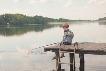 Boy sitting and fishing from a dock on lake or river