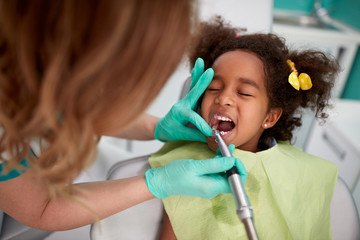 Female dentist patiently polish teeth to child  .