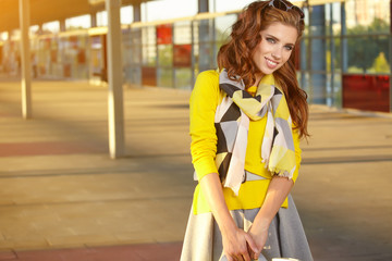 Beautiful young woman with luggage is waiting a train