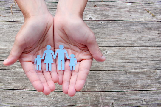 Paper family in hands on wooden background welfare concept