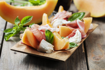 Antipasto with melon, mozzarella, ham and basil