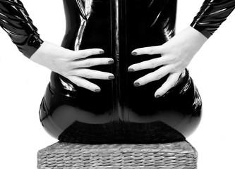 Donna con abito aderente in pelle seduta di spalle con le mani appoggiate sulla schiena