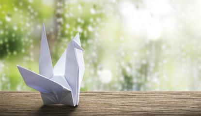 Origami paper crane in rainy day