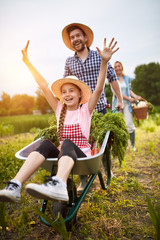 Girl having fun with farmer in vegetables garden
