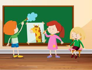 Three students drawing on blackboard
