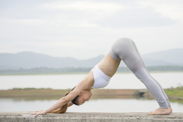 Woman practicing Yoga Downward facing dog pose in the morning