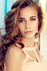 fashion interior photo of beautiful young girl with dark curly hair and tender makeup