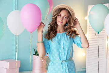 fashion interior photo of beautiful young girl with dark curly hair and tender makeup, posing with colorful air balloons
