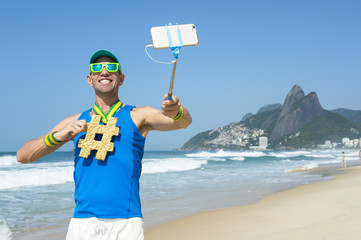 Hashtag gold medal athlete posing for a photo with his mobile phone on a selfie stick on Ipanema Beach in Rio de Janeiro, Brazil