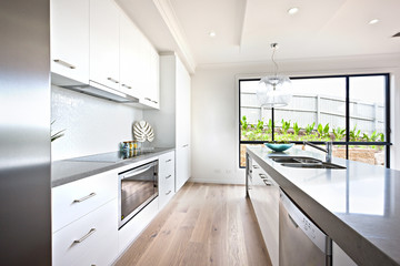 Kitchen counter top with wooden floor beside a window