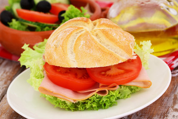Lunch consisting of bread roll with chicken, tomatoes and lettuce and bowl of salad