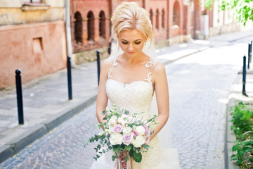 Romantic bride with her amazing bouquet alone