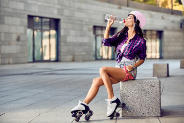 Hipster girl drink water and resting after active time in urban skate park. Young woman sitting on a stone bench. Portrait of beautiful brunette girl in roller skates and a pink helmet.
