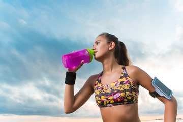 Young fit girl drinking water on beach after morning workout