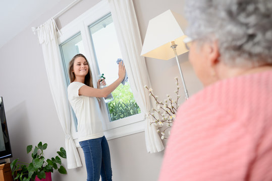 cheerful young girl helping with household chores elderly woman at home