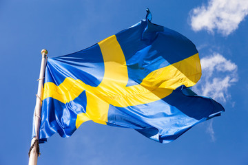 Swedish flag waving in the wind on a blue sky background