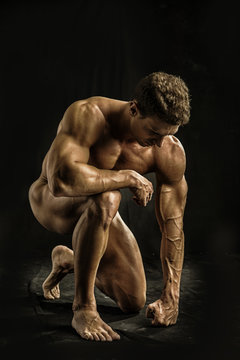 Totally Nude Young Muscle Man Crouching on one Knee in Studio with Black Background