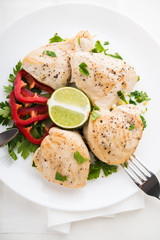 Chicken breasts with parsley, pepper and citrus on white wood background top view. Healthy food.