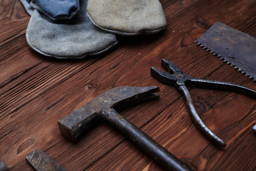 A carpenter's hand tool kit over wooden background