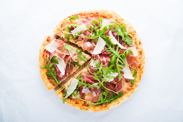 Sliced pizza with prosciutto (parma ham), arugula (salad rocket) and parmesan on white background top view. Italian cuisine.