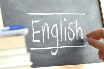 "Hand writing on a blackboard in a language class with the word ""English"" wrote on. Some books and school materials."