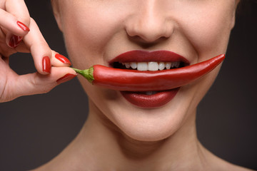 Passionate woman eating hot chili