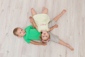 Little boy and girl lying on the floor.