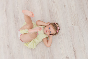 Little handsome girl with blue eyes lying on the floor