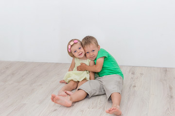 Beautiful boy and girl sitting on the floor and hugging
