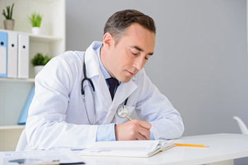 Portrait of adult doctor sitting at his desk