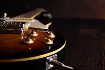 Old electric guitar on wooden table and background