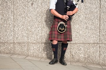 bagpiper dressed in kilt playing bag pipes
