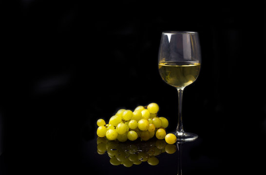 glass of white wine with grapes on a black background with reflection and water drops