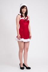 女性のモデルが、サンタクロースの衣装を着て立っています。この写真の背景は、白です。