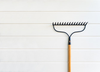 Minimalist image of new rake hanging on clean white wooden texture wall with copy space