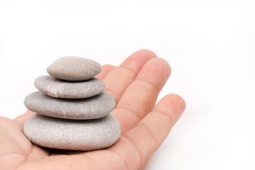 Balanced grey stones in hand