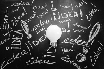 Light bulb  on the black chalkboard with titles idea, light bulb idea , business idea , business concept ,Innovation concept