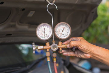Dirty hands holding a manometers on equipment for filling air conditioners
