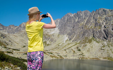 Young blonde woman taking photographs of lake and mountain