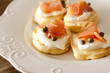 Raw fish Blini snacks on plate