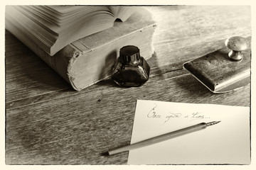 """Phrase """"Once upon a time"""" handwritten, surrounded with a fountain pen, an ink pot, a blotting paper holder and old books. Selective focus. Grain noise added. Post processed to look like an old photo."""