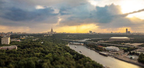 Tilt and shift view of rainy Lenin hills area with river reflections, boats, sport stadium and profile of Moscow university main building on horizon line
