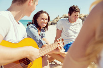 Beautiful young people with guitar on beach