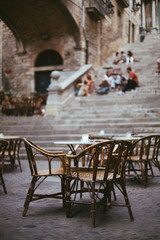 Empty outdoor cafe in old town. Street restaurant. Menu of Mediterranean tasty food. Evening daytime. Time for evening meal.  People sitting on the steps and talking